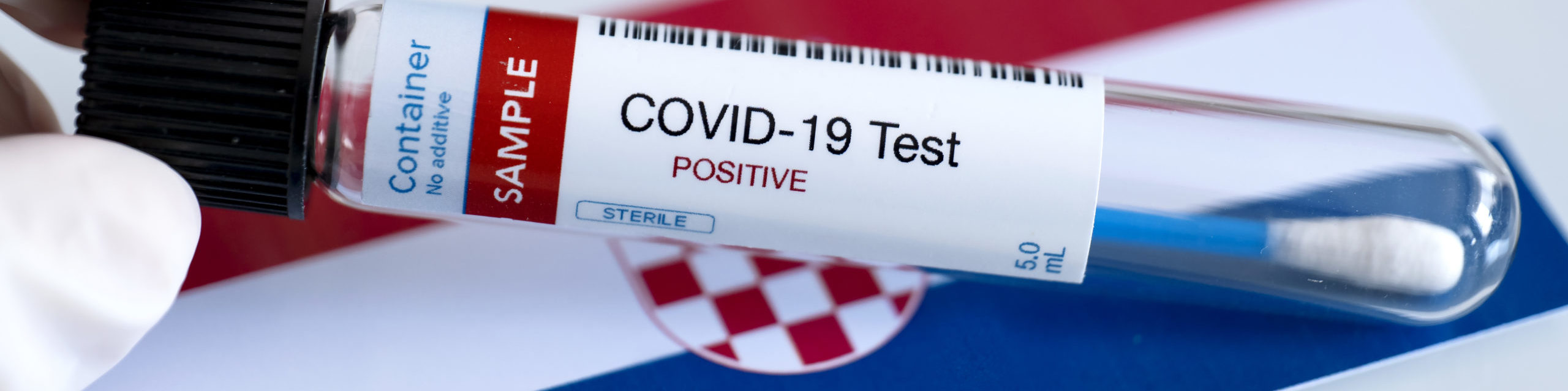Testing for presence of coronavirus in Croatia. Tube containing a swab sample that has tested positive for COVID-19. Croatian flag in the background.